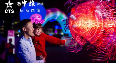 Family enjoying a close-up view of the Fugu light installation at First Fleet Park, The Rocks during Vivid Sydney 2018