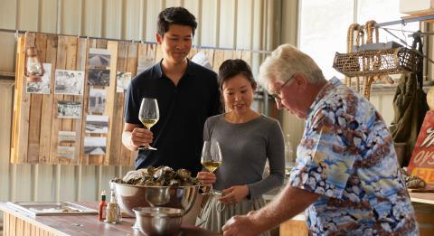 夫妇与格林威尔点吉姆·怀尔德的牡蛎的吉姆·怀尔德一起享用新鲜开放的牡蛎