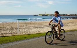 在卧龙岗 (Wollongong) 的卧龙岗海滩 (Wollongong Beach) 上骑自行车游览